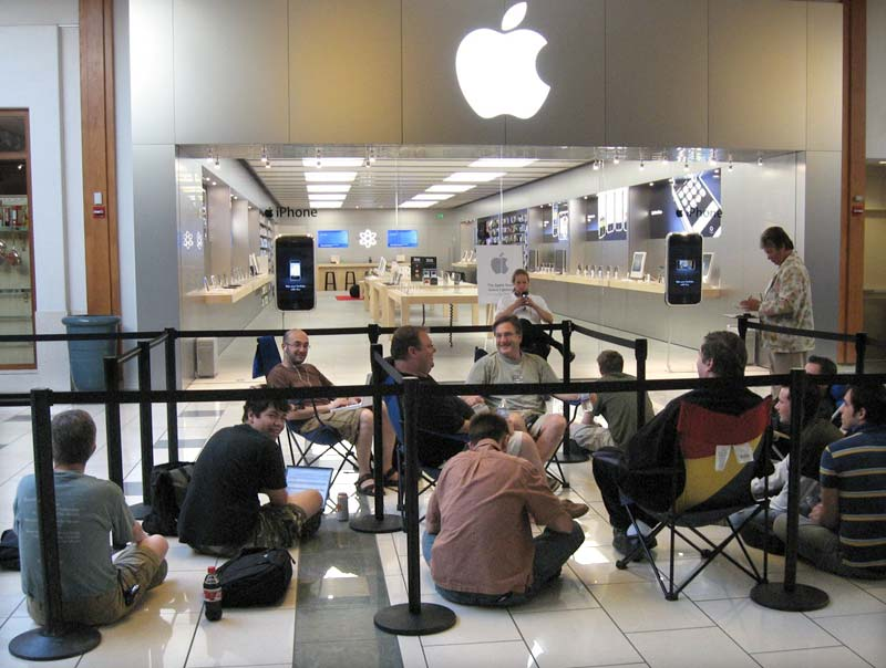 people sitting and waiting outside Apple store